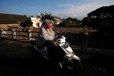 A woman rides a motorbike as she passes a bridge near a river covered by rubbish in Bekasi, West Java province, Indonesia, January 7, 2019. REUTERS/Willy Kurniawan/Files