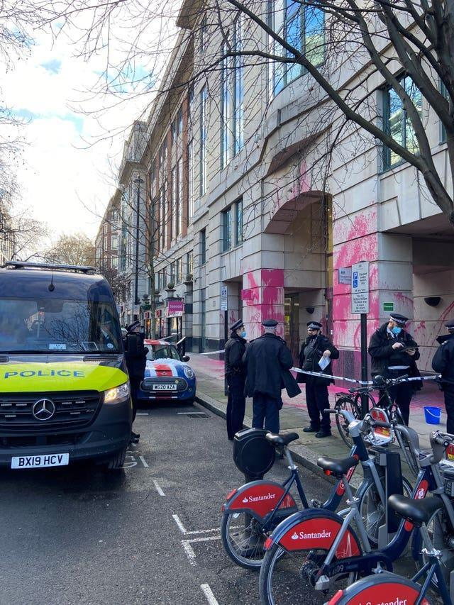 Police outside the Department for Transport, which has been vandalised with pink paint