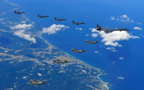 A US Air Force B-1B Lancer bomber (right), US F-35B stealth jet fighters (bottom) and South Korean F-15K fighter jets (top) flying over South Korea - Credit: AFP