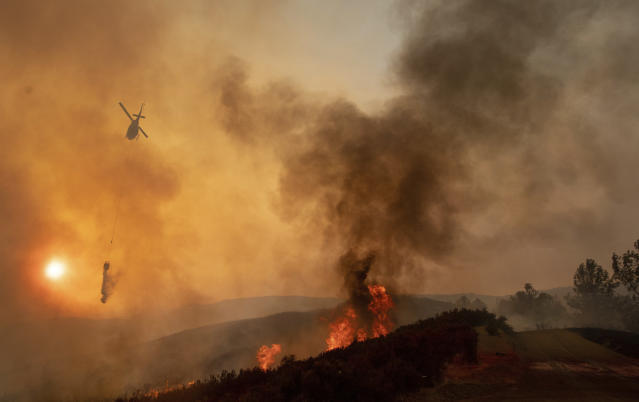 <p>A helicopter drops water on a burning hillside during the Ranch Fire in Clearlake Oaks, Calif., Sunday, Aug. 5, 2018. (Photo: Josh Edelson/AP) </p>