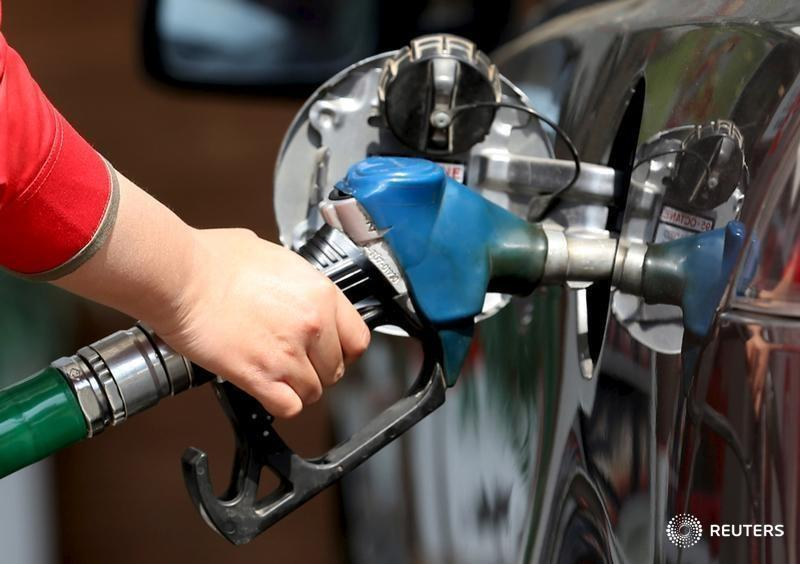A female employee fills the tank of a car at a petrol station in Cairo
