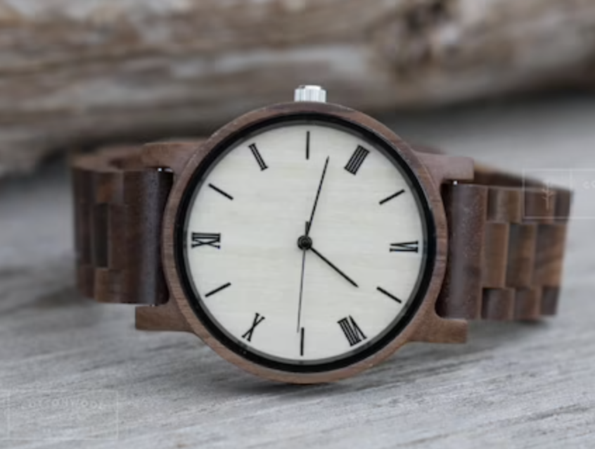 brown wooden watch laying on its side on wooden background
