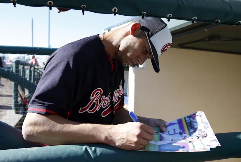 Atlanta Braves shortstop Andrelton Simmons signs an autograph for a fan during a spring training baseball workout, Tuesday, Feb. 18, 2014, in Kissimmee, Fla. (AP Photo/Alex Brandon)