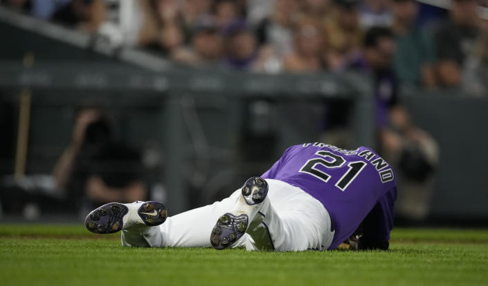 Colorado Rockies starting pitcher Kyle Freeland falls to the ground after being hit by a single off the bat of Chicago Cubs' Andrew Romine in the fifth inning of a baseball game Tuesday, Aug. 3, 2021, in Denver. Freeland remained on the mound through the inning but was pulled in the top of the sixth. (AP Photo/David Zalubowski)