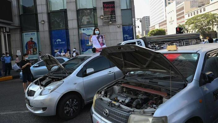 Cars with open hoods are parked to block a road during a demonstration against the military coup in Yangon on February 17, 2021