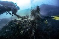 Divers untangle a fishing net caught around a reef off the coast of Thailand