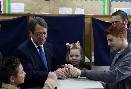 Presidential candidate Nicos Anastasiades casts his vote with some help from his grandchildren, during the second round of the presidential election in Limassol, Cyprus February 4, 2018. REUTERS/Yiannis Kourtoglou