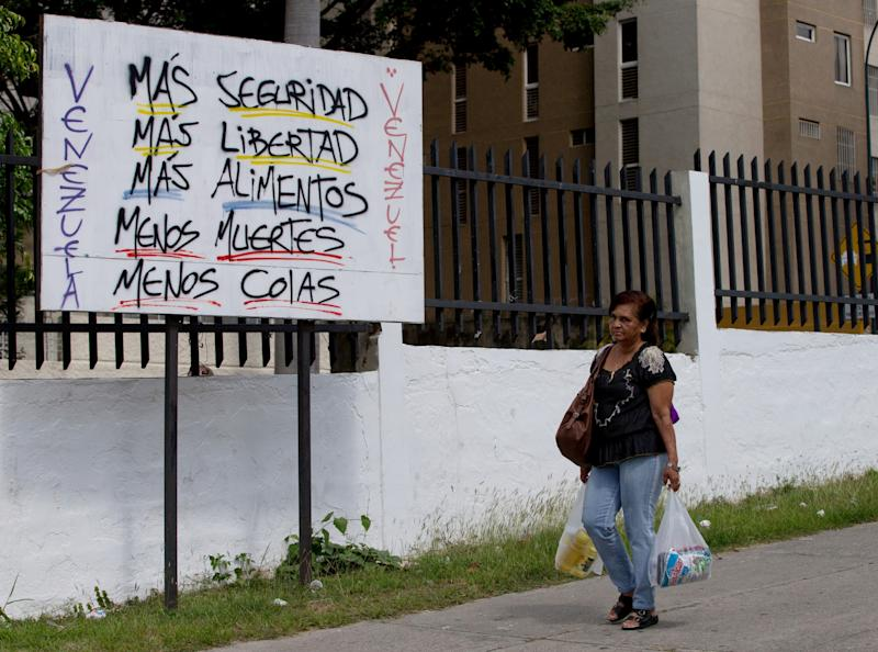 """A woman carries powdered milk and cooking oil she bought from the state-run supermarket Bicentenario as she walk by a poster that reads in Spanish """"Venezuela, more security, more freedom, more food, fewer deaths, less lines"""" near the Petare shantytown in Caracas, Venezuela, Friday, Jan. 16, 2015. Venezuela's crisis has been long in the making. Even before collapsing oil prices strangled its foreign revenue stream, the country was stuck in a year-old recession and its inflation rate racing toward triple digits. (AP Photo/Fernando Llano)"""