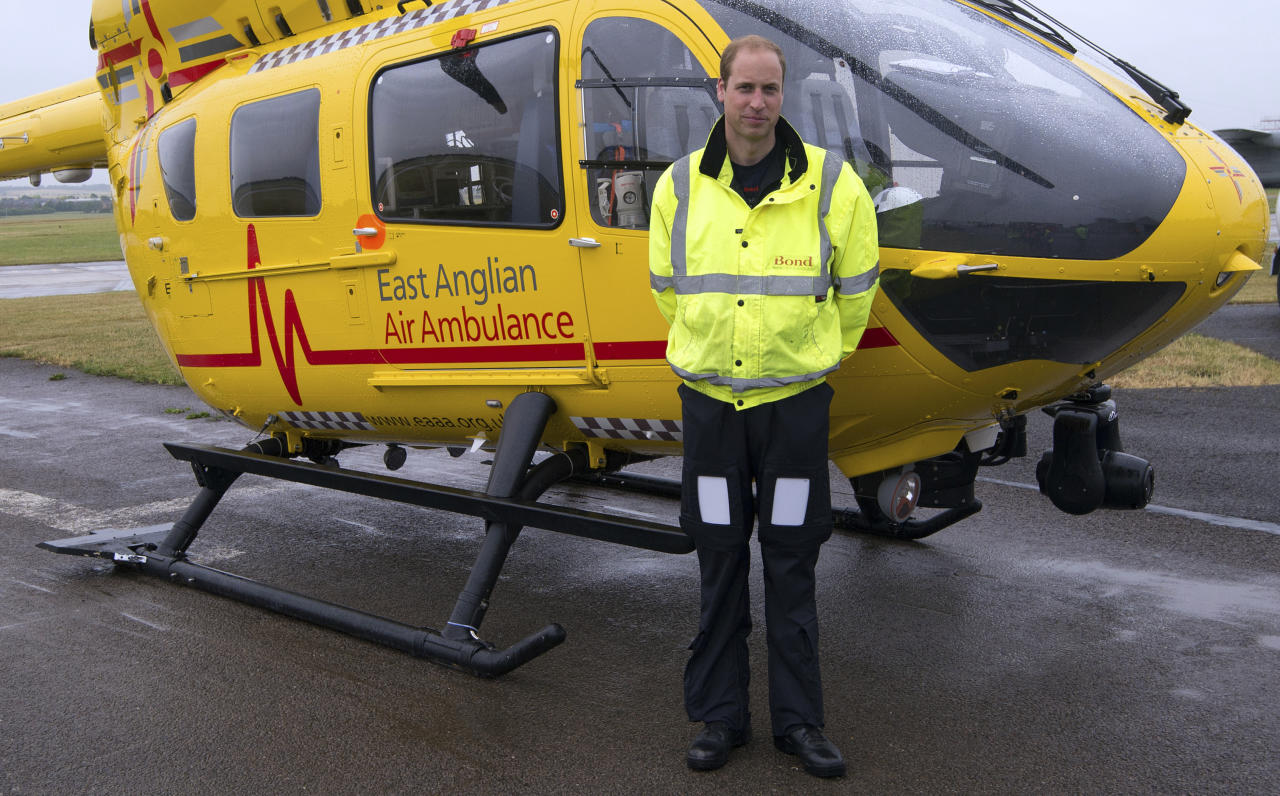 FILE - This is a Monday July 13, 2015 file photo of Britain's Prince William, as he poses in front of an East Anglian Air Ambulance (EAAA) as he begins his new role, at Cambridge Airport, Cambridge, in England. Prince William is completing his final shift in his job as an air ambulance pilot as he gets ready to take on more extensive royal duties. The heir to the British throne is working the night shift Thursday July 27, 2017 at the East Anglian Air Ambulance, where he has been flying medical crews to emergencies such as traffic accidents for about two years. (Stefan Rousseau, Pool, File via AP)