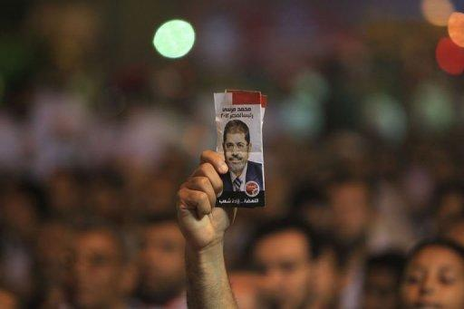A supporter of Mohammed Mursi holds a leaflet depicting Mohammed Mursi during a campaign rally in Cairo on May 20. Initial results of expatriate voting showed Muslim Brotherhood candidate Mursi leading the race thanks to massive support from the Egyptian community in Saudi Arabia