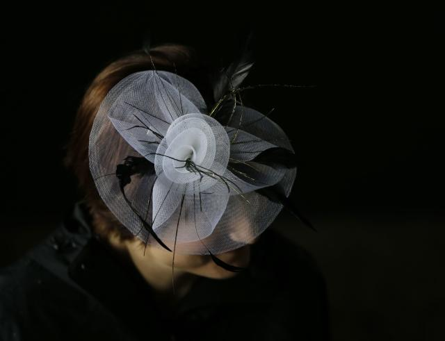 A spectator arrives with her fancy hat during the 139th Kentucky Derby at Churchill Downs Saturday, May 4, 2013, in Louisville, Ky. (AP Photo/Matt Slocum)