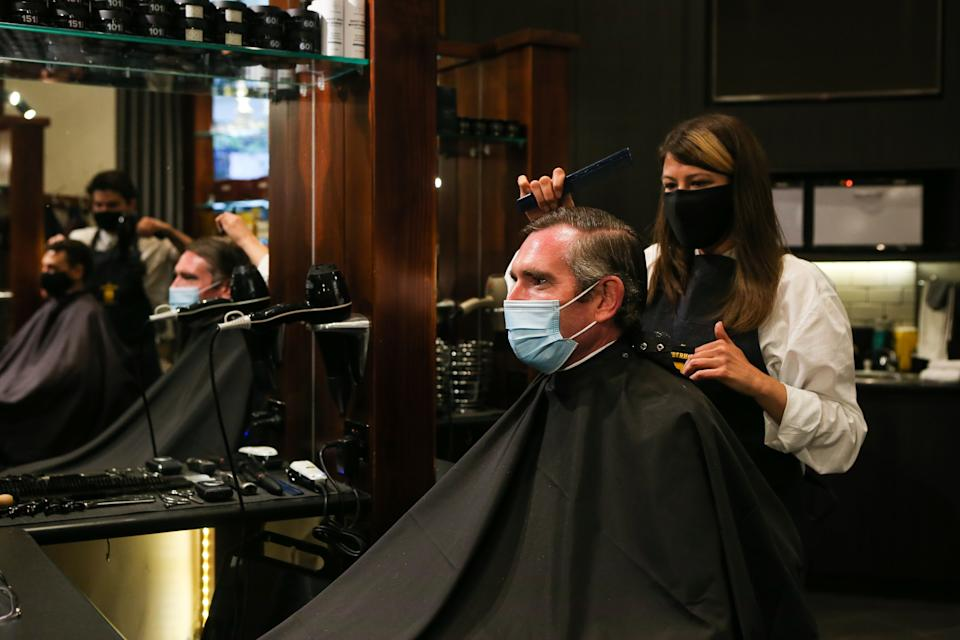 SYDNEY, AUSTRALIA - OCTOBER 11: NSW Premier Dominic Perrottet receives a haircut at Barberhood men's hair stylists on October 11, 2021 in Sydney, Australia. COVID-19 restrictions have eased across NSW today after the state passed its 70 per cent double vaccination target. Under the state government's Reopening NSW Roadmap, people who are fully vaccinated are permitted to have 10 visitors in their homes, and outdoor gatherings can have up to 20 people. Hospitality, retail stores, gyms and hairdressers can reopen, as well as cinemas, theatres, museums and galleries. Indoor pools are also able to reopen and up to 500 people can attend ticketed outdoor events. Weddings and funerals are permitted to have up to 100 people provided all adults have received two doses of a COVID-19 vaccine. Churches and places of worship can open with no singing. Restrictions will ease further in NSW once the state reaches its next vaccination milestone of 80 per cent of people having received two doses of a COVID-19 vaccine. (Photo by Gaye Gerard - Pool/Getty Images)