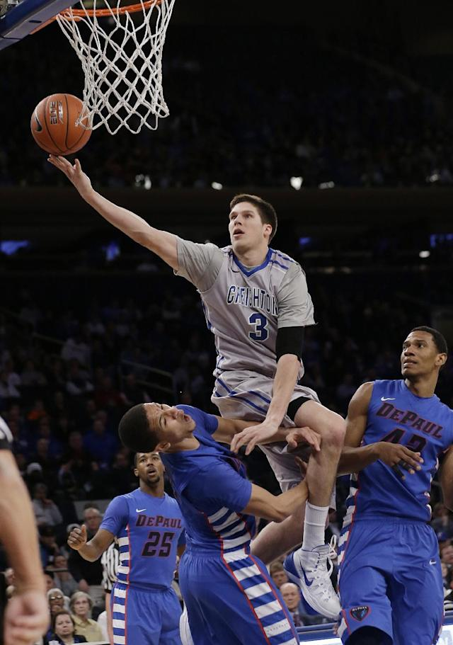 FILE - In this March 13, 2014 file photo, Creighton's Doug McDermott (3) splits DePaul's Billy Garrett Jr. (5) and Greg Sequele (42) to score during the first half of an NCAA college basketball game in the quarterfinals of the Big East Conference tournament at Madison Square Garden in New York. McDermott, who finished his career at Creighton as college basketball's fifth-leading scorer, is a near-unanimous selection as The Associated Press' player of the year, Thursday, April 3, 2014. (AP Photo/Frank Franklin II, File)