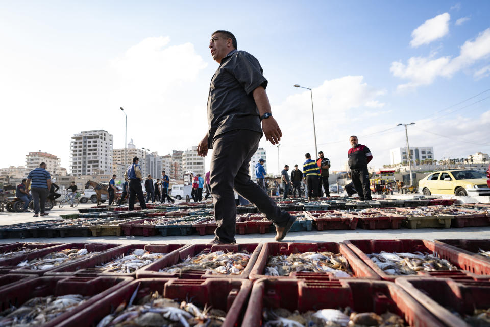 Lots of seafood are organized on the ground as buyers browse the day's catch at auction after a limited number of boats were allowed to return to the sea following a cease-fire reached after an 11-day war between Hamas and Israel, in Gaza City, Sunday, May 23, 2021. (AP Photo/John Minchillo)