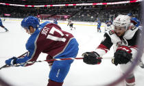 Colorado Avalanche center Tyson Jost, left, clears the puck as Arizona Coyotes center Nick Schmaltz pursues in the third period of an NHL hockey game Monday, April 12, 2021, in Denver. (AP Photo/David Zalubowski)