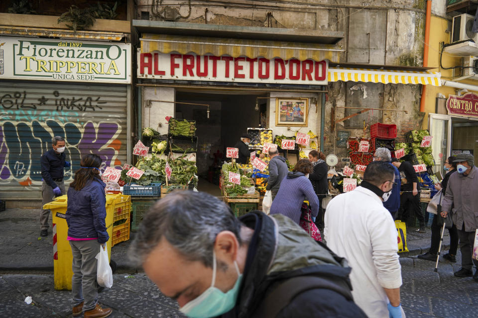 People buy fruit and vegetables at a shop in Naples, Monday, April 27, 2020. Region Campania allowed cafes and pizzerias to reopen for delivery Monday, as Italy is starting to ease its lockdown after a long precautionary closure due to the coronavirus outbreak. (AP Photo/Andrew Medichini)