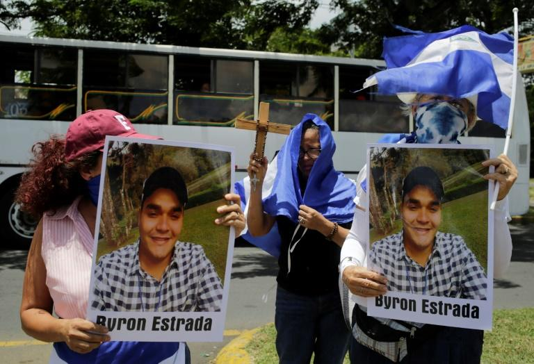 "Anti-government protesters hold the portrait of a political prisoner as they form a ""Human Chain"" in Managua on August 30, 2018. Some three hundred Nicaraguans formed a human chain along the road linking Metrocentro roundabout and the Central American University (UCA) demanding the release of political prisoners"