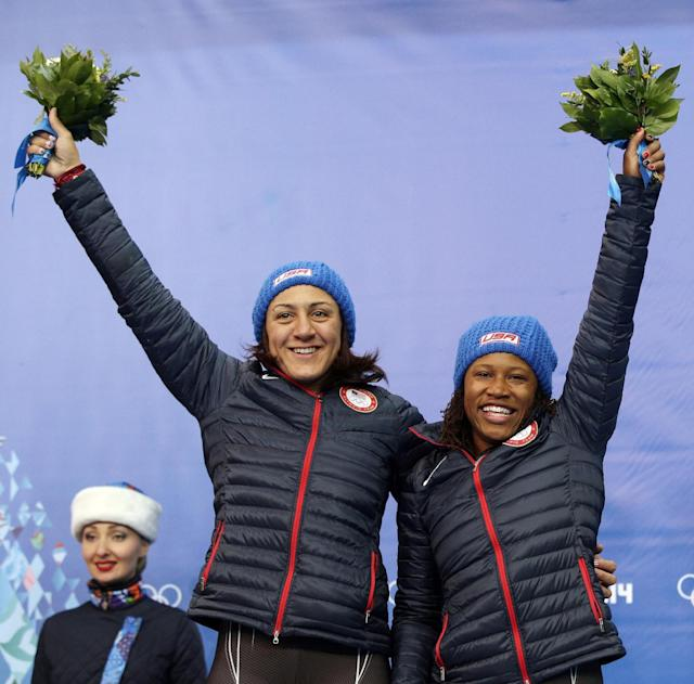 Silver medal winners from the United States Elana Meyers and Lauryn Williams, pose during the flower ceremony during the women's bobsled competition at the 2014 Winter Olympics, Wednesday, Feb. 19, 2014, in Krasnaya Polyana, Russia. (AP Photo/Michael Sohn)