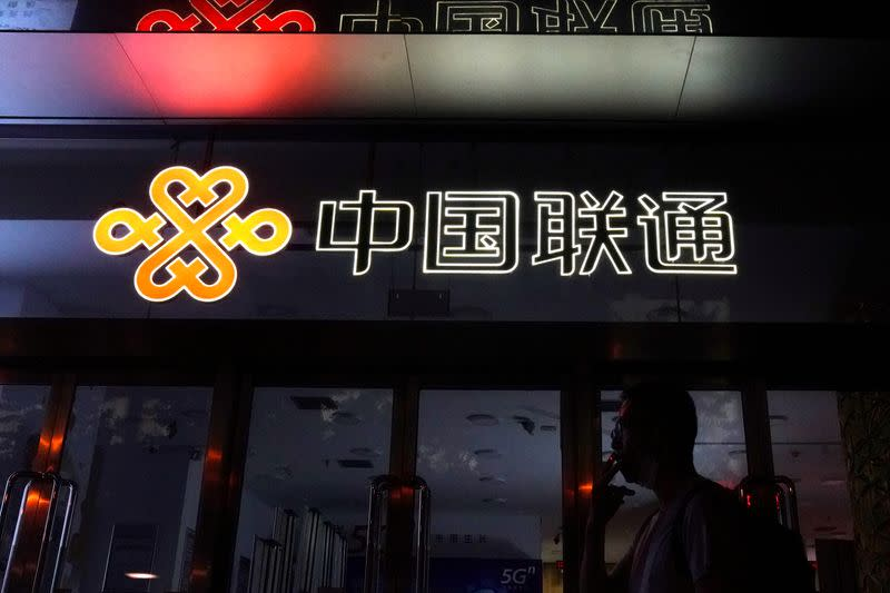 FILE PHOTO: Man smokes in front of a China Unicom store in Beijing