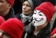 """A protester wearing a red cap, the symbol of protest in Brittany, and a Guy Fawkes mask takes part in a demonstration to maintain jobs in the region and against an """"ecotax"""" on commercial trucks, in Carhaix, western France, November 30, 2013. REUTERS/Mal Langsdon"""