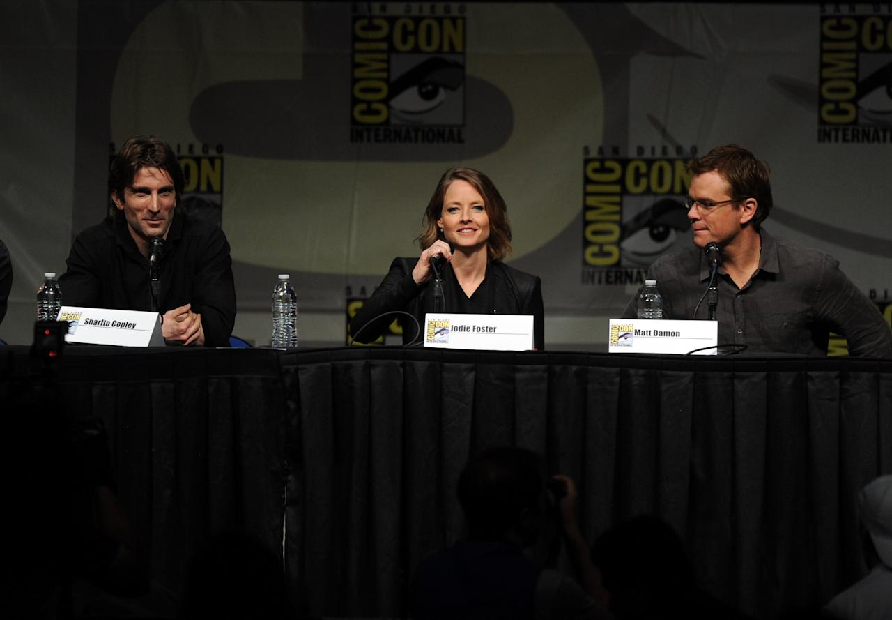 """SAN DIEGO, CA - JULY 13:  Actors Sharlto Copley, Jodie Foster, and actor Matt Damon speak during Sony's """"Eylsium"""" panel during Comic-Con International 2012 at San Diego Convention Center on July 13, 2012 in San Diego, California.  (Photo by Kevin Winter/Getty Images)"""