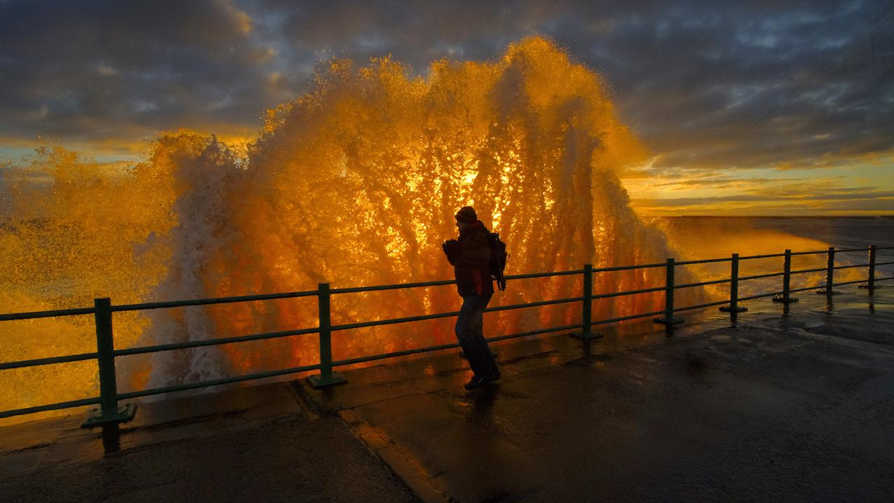 'Sunrise Through The Wave', by John Alderson, which has won the People category of the UK's Ultimate Sea View photography competition (Picture: PA)