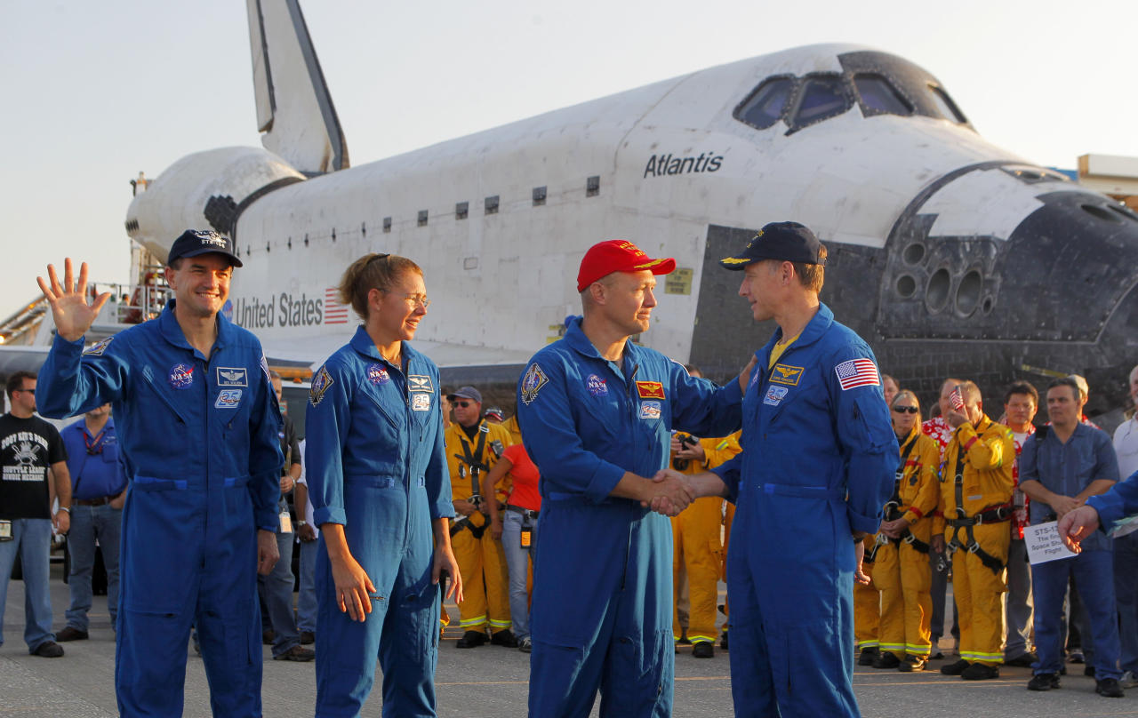 Commander Chris Ferguson, right, shakes hands with pilot Doug Hurley after landing Space Shuttle Atlantis at the Kennedy Space Center at Cape Canaveral, Fla. Thursday, July 21, 2011. The landing of Atlantis marks the end of NASA's 30 year space shuttle program. Third from right is mission specialist Sandra Mangus and Rex Walheim. (AP Photo/Scott Audette, Pool)