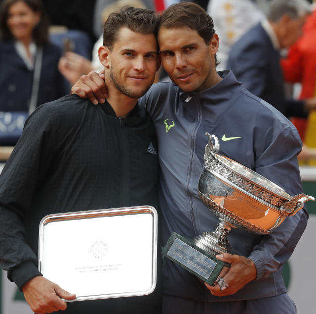 Spain's Rafael Nadal, right, holds the trophy as he celebrates his record 12th French Open tennis tournament title after winning his men's final match against Austria's Dominic Thiem, left, in four sets, 6-3, 5-7, 6-1, 6-1, at the Roland Garros stadium in Paris, Sunday, June 9, 2019. (AP Photo/Michel Euler)
