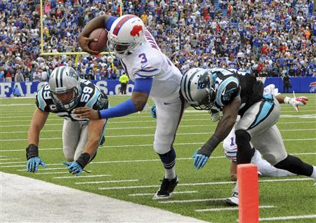 Buffalo Bills quarterback EJ Manuel (C) is knocked out of bounds by Carolina Panthers cornerback Captain Munnerlyn (R) and linebacker Luke Kuechly late in the fourth quarter of their NFL football game in Orchard Park, New York September 15, 2013. Buffalo won 24-23. REUTERS/Don Heupel