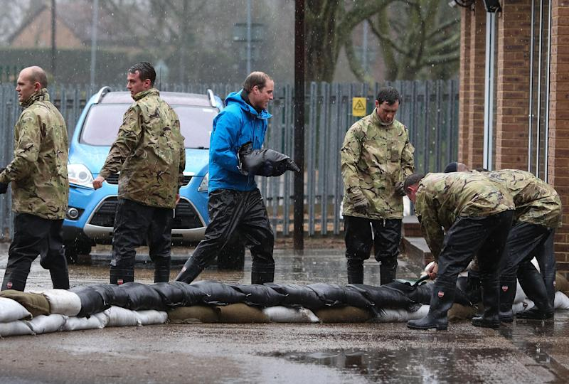 Britain's Prince William, The Duke of Cambridge, centre, unloads sandbags, with members of the armed forces, in Datchet, England, Friday Feb. 14, 2014. Prince William and Prince Harry helped flood-hit U.K. villagers protect their homes, unloading sandbags alongside soldiers in the River Thames village of Datchet. The princes, who have both served in the armed forces, joined a work crew Friday on what aides called a private visit. (AP Photo/Ki Price, PA) UNITED KINGDOM OUT - NO SALES - NO ARCHIVES