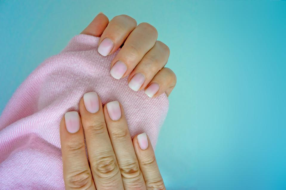 Beautiful gradient manicure. White and pink ombre on both hands. Light blue background.