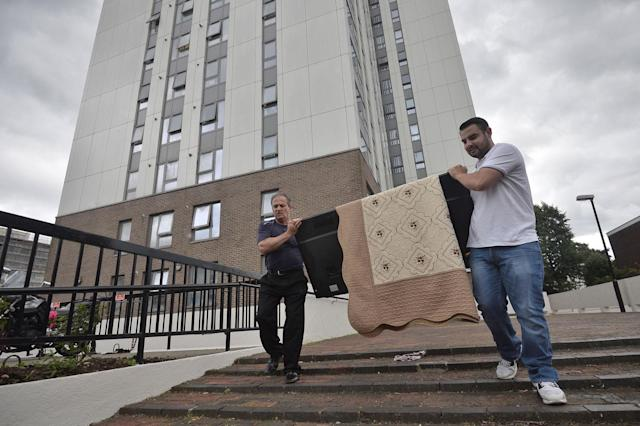 <p>Two men carry a television set from the Dorney Tower residential block, as residents were evacuated as a precautionary measure following concerns over the type of cladding used on the outside of the buildings on the Chalcots Estate in north London, Britain, June 25, 2017. (Photo: Hannah McKay/Reuters) </p>
