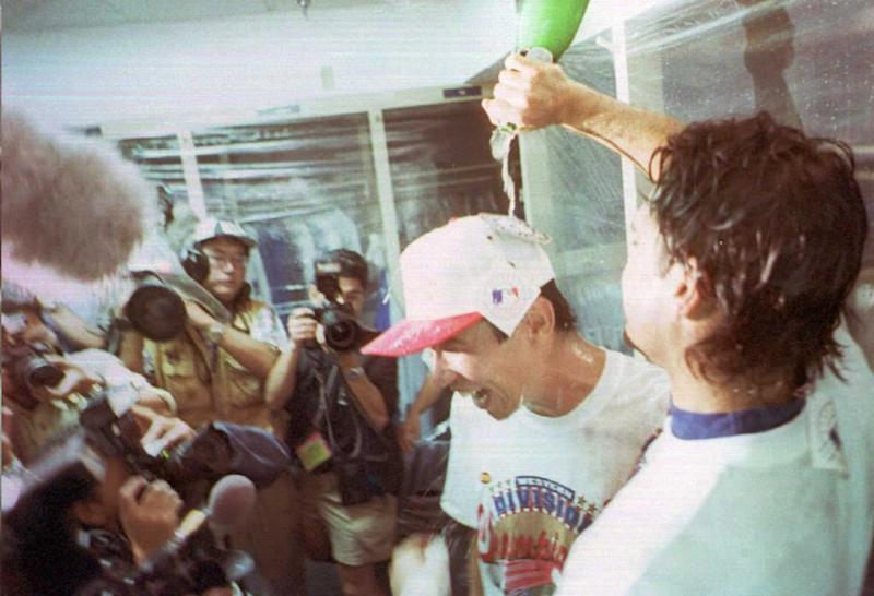 Hideo Nomo has champagne poured over his head after a win that clinched at least a tie of the NL West title.