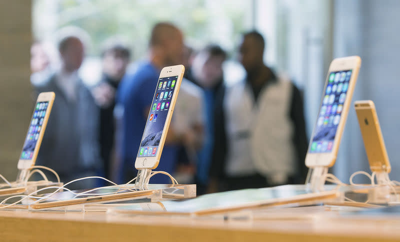 Customers stand in line at the Apple store in Berlin, as they wait to buy the newly released iPhone 6