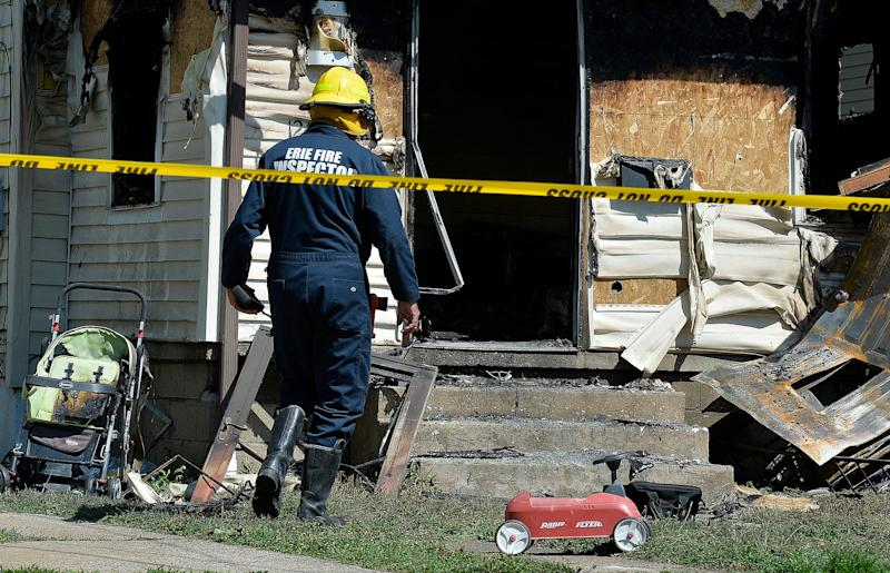 Erie Bureau of Fire Inspector Mark Polanski works at the scene of a fatal house fire on Sunday in Erie, Pa.