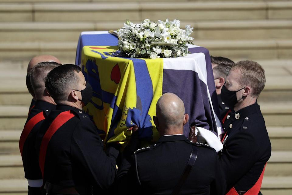 <p>Prince Philip's casket, covered in his personal standard and flowers, is carried into the chapel. </p>