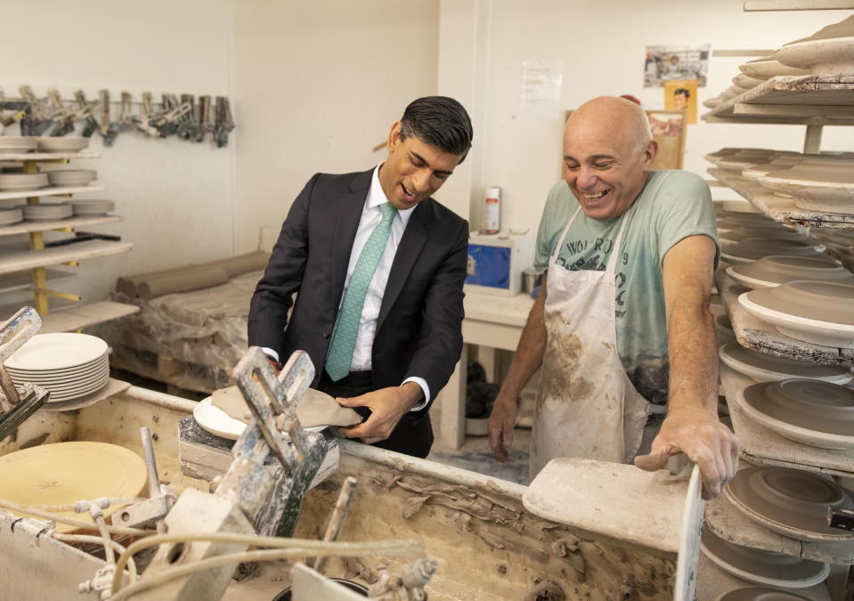 STOKE-ON-TRENT, ENGLAND - SEPTEMBER 14: Chancellor Rishi Sunak learns the art of handling clay to make plates with Wayne Swindaill during a visit to the Emma Bridgewater pottery after employees returned back to work after being furloughed on September 14, 2020 in Stoke-on-Trent, England. (Photo by Andrew Fox - WPA Pool / Getty Images)