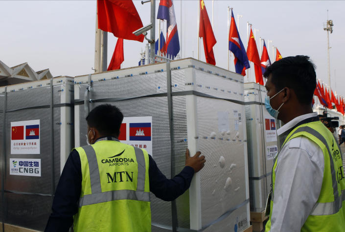 """Workers pull boxes loaded with COVID-19 vaccines before a handing over ceremony at Phnom Penh International Airport, in Phnom Penh, Cambodia, Sunday, Feb. 7, 2021. Cambodia on Sunday received its first shipment of COVID-19 vaccine, a donation of 600,000 doses from China, the country's biggest ally. Beijing has been making such donations to several Southeast Asian and African nations in what has been dubbed """"vaccine diplomacy,"""" aimed especially at poorer countries like Cambodia. (AP Photo/Heng Sinith)"""