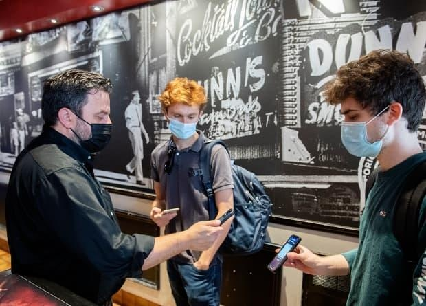 Jimmy Staveris, left, manager of Dunn's Famous restaurant in Montreal, scans the QR code of a client as the Quebec government's COVID-19 vaccine passport comes into effect. (Graham Hughes/The Canadian Press - image credit)