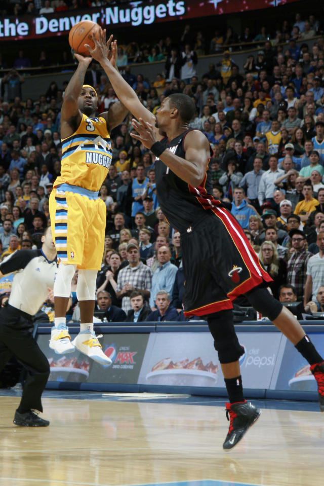 Denver Nuggets guard Ty Lawson, left, misses a shot as Miami Heat center Chris Bosh covers late in the fourth quarter of the Heat's 97-94 victory in an NBA basketball game in Denver on Monday, Dec. 30, 2013. (AP Photo/David Zalubowski)