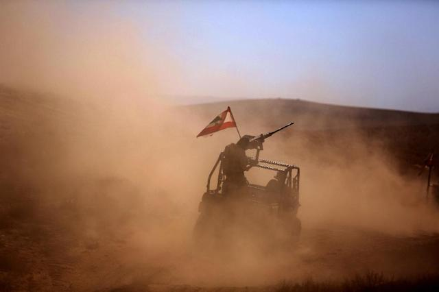 Lebanese soldiers drive a buggy bearing the Lebanese flag in an area they recently took from the Islamic State (IS) group in Jurud Ras Baalbek on the Syrian-Lebanese border, on August 28, 2017 (AFP Photo/PATRICK BAZ)