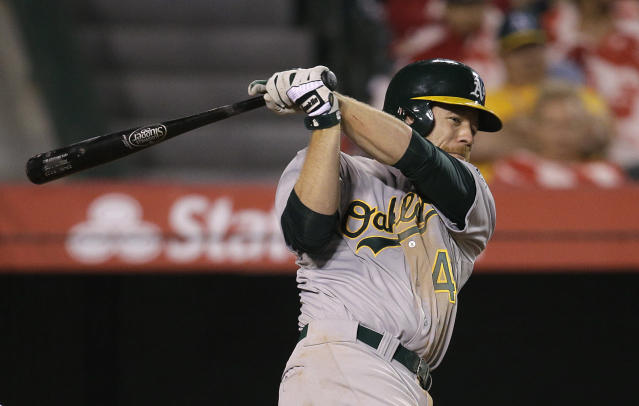 Oakland Athletics' Brandon Moss hits a RBI single during the eighth inning of a baseball game against the Los Angeles Angels on Tuesday, April 15, 2014, in Anaheim, Calif. (AP Photo/Jae C. Hong)