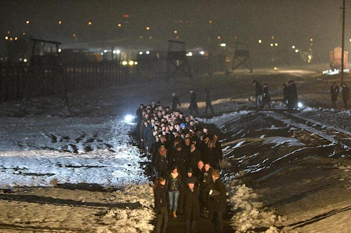 Poland's President Bronislaw Komorowski (C) and guests walk in a procession to light candles on a memorial for the victims after the main ceremony to mark the 70th anniversary of the liberation of the Auschwitz death camp on January 27, 2015 (AFP Photo/Janek Skarzynski)