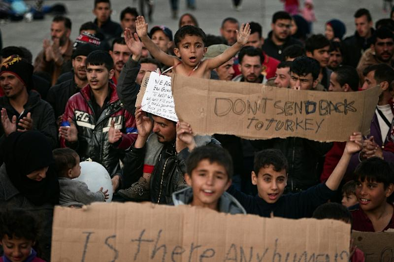 "Adults and children shout, ""No Turkey"" a the port at the town of Chios where refugees and migrants who broke out from Vial detention center are camped out on April 3, 2016 (AFP Photo/Louisa Gouliamaki)"