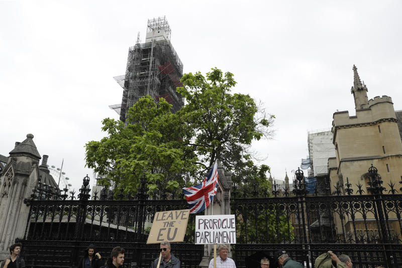Brexit supporters holds placards as they protest outside the scaffolding-covered Big Ben at the Houses of Parliament in London, Tuesday, June 18, 2019. All six contenders to replace British Prime Minister Theresa May as leader of the ruling Conservative party vow they will succeed where May failed and lead Britain out of the European Union, though they differ about how they plan to break the country's Brexit deadlock. (AP Photo/Matt Dunham)