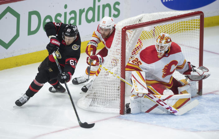 Calgary Flames goaltender Jacob Markstrom keeps an eye on the puck as defenseman Noah Hanifin chases Ottawa Senators right wing Evgenii Dadonov around the net during the second period of an NHL hockey game Wednesday, March 24, 2021, in Ottawa, Ontario. (Adrian Wyld/The Canadian Press via AP)