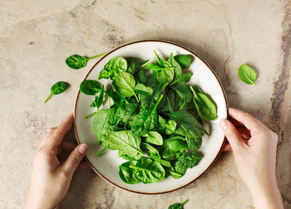 Woman's hands holding a plate with fresh spinach, top view. (Photo by: Anjelika Gretskaia/REDA&CO/Universal Images Group via Getty Images)