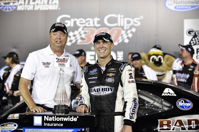FILE - In this Aug. 30, 2014, file photo, Kevin Harvick, right, poses with Atlanta Motor Speedway president Ed Clark after winning the NASCAR Nationwide Cup Series auto race at Atlanta Motor Speedway in Hampton, Ga. The Labor Day weekend slot in NASCAR's schedule no longer looks appealing to Clark. The track is serving as one of the final set-up races for the Chase for the Sprint Cup for the final time on Sunday night. (AP Photo/David Tulis, File)