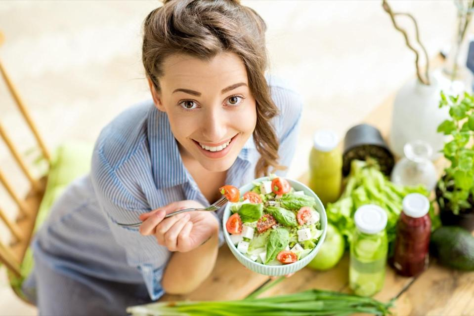 Happy woman eating healthy salad sitting on the table with green fresh ingredients indoors