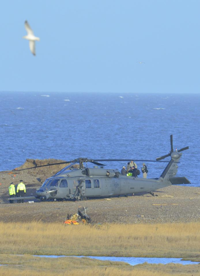 A Pave Hawk helicopter, military personnel and emergency services attend the scene of a helicopter crash on the coast near the village of Cley in Norfolk, eastern England January 8, 2014. British police said on Wednesday they would be working with the U.S. Air Force and others to find out why a U.S. military helicopter crashed on the coast of eastern England, killing all four crew on board. The helicopter, a Pave Hawk assigned to the 48th Fighter Wing based at RAF Lakenheath air base, was performing a low-level training mission along the Norfolk coast when it went down in marshland on Tuesday evening. The helicopter pictured is not the crashed helicopter but a second helicopter, which had been taking part in the same training exercise as the one that crashed. REUTERS/Toby Melville (BRITAIN - Tags: MILITARY DISASTER TPX IMAGES OF THE DAY)
